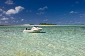 Boat anchored in shallow tropical water, Aitutaki,The Cook Islands