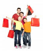 stock photo of stand up  - Happy family with shopping bags standing at studio over white background - JPG