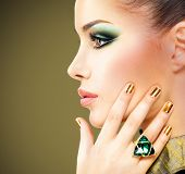 stock photo of precious stones  - Glamour woman with beautiful golden nails and emerald ring on hands - JPG