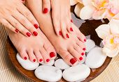 image of fingernail  - Closeup photo of a beautiful female feet at spa salon on pedicure procedure - JPG