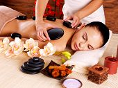 foto of backbone  - Adult woman having hot stone massage in spa salon - JPG