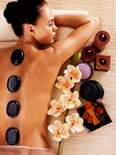 Adult woman relaxing in spa salon with hot stones on body. Beauty treatment therapy