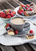 stock photo of eclairs  - Cup of coffee and chocolate eclairs with fresh berries - JPG