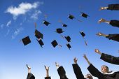 foto of graduation hat  - Students throwing graduation hats in the air celebrating with blue sky - JPG