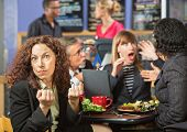 foto of clenched fist  - Angry woman with clenched fists at table with coworkers - JPG