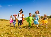 stock photo of happy halloween  - Six happy diverse looking boys and girls running in the field wearing Halloween costumes - JPG