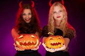 foto of antichrist  - Two carved Halloween pumpkins held by females - JPG