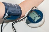 picture of sphygmomanometer  - Sphygmomanometer measuring blood pressure on an arm - JPG