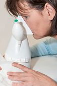 stock photo of inhalant  - Woman is sitting in front of an inhaler and is inhaling - JPG