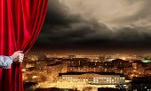 stock photo of opulence  - Hand of businessman opening red velvet curtain - JPG