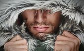 picture of macho man  - brutal face of a man with beard bristles and hooded winter - JPG
