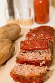 pic of meatloaf  - Sliced meatloaf on a wood cutting board with baked potatoes