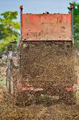 image of tractor-trailer  - Tractor with trailer fertilizing field with natural manure - JPG