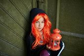 stock photo of antichrist  - Portrait of Halloween girl holding lantern with candle and looking at camera - JPG