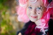 foto of antichrist  - Cute girl with painted eyelashes and pink wig looking at camera with smile - JPG