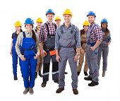 image of dungarees  - Confident diverse team of workmen and women standing grouped in their dungarees and hardhats smiling at the camera high angle view isolated on white - JPG