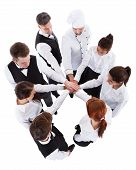 pic of waiter  - High angle view of waiters and waitresses stacking hands - JPG