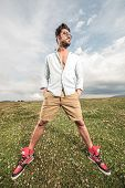 foto of legs apart  - Handsome man posing on a field of grass with his legs apart - JPG