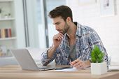 stock photo of single man  - Man working from home with laptop and taking notes - JPG