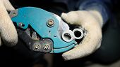 stock photo of pipe-welding  - Close up view on pipe cutter with plastical pipe - JPG