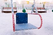 foto of snow-slide  - snow covered swing and slide at a playground in winter - JPG