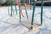 pic of snow-slide  - snow covered swing and slide at a playground in winter - JPG