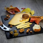 stock photo of solid  - Solid cheeses plate: Dutch Gouda cheese olives provencal walnuts and autumn leaves
