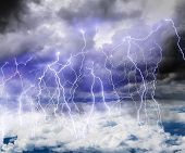 foto of lightning  - Black clouds in the sky full of lightning in a thunderstorm with a roll of Thunder - JPG