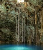 picture of cenote  - Beautiful natural pool of Cenote Xkenken in underground cavern with crystal clear blue water and vines and stalactites hanging from ceiling in Dzitnup Yucatan Mexico - JPG