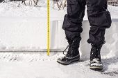 stock photo of measuring height  - Man measuring the height of the snowfall - JPG
