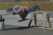 foto of concrete pouring  - A builder uses a sawhorse and plank to position himself while floating off new concrete for a large building near Greymouth South Island New Zealand  - JPG