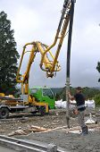 stock photo of concrete pouring  - Builder uses a concrete pump to direct wet concrete into the foundations of a large building - JPG