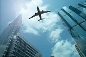pic of noise pollution  - Airplane in the sky with modern buildings - JPG