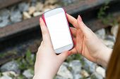 stock photo of dial pad  - Young woman holding and showing smart phone with blank white empty screen on blurry stones and railway background - JPG