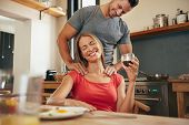 foto of shoulders  - Happy young woman sitting at breakfast tablet holding cup of coffee getting a shoulder massage from her boyfriend - JPG
