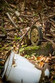 stock photo of illegal  - illegal garbage dump in the middle of the forest, rusty bucket ** Note: Shallow depth of field - JPG