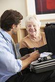 foto of visitation  - Doctor visiting senior woman at home - JPG