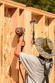 image of partition  - Building contractor worker putting in a interior wall partition nailer wall for the first floor on a new home construciton project - JPG
