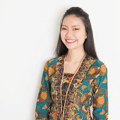 image of southeast asian  - Portrait of Southeast Asian woman in batik dress on plain background - JPG
