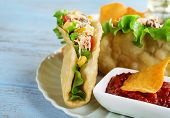 foto of tacos  - Tasty taco with tomato dip on plate and vegetables on table close up - JPG