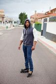 picture of hooded sweatshirt  - Hooded afroamerican guy with skates on the street with a wall background - JPG