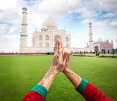 stock photo of namaste  - Woman hands with henna painting in Namaste gesture near Taj Mahal in Agra Uttar Pradesh India - JPG