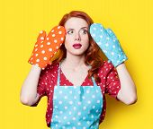 stock photo of redhead  - Surprised redhead girl in red polka dot dress and mittens on yellow background - JPG