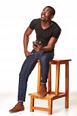 stock photo of people talking phone  - Portrait of smiling african man sitting on the chair and  talking on the phone - JPG