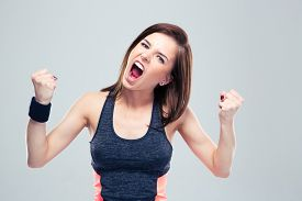 picture of shout  - Angry young sports woman shouting on gray background and looking at camera - JPG