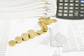 pic of piles  - Bankruptcy of house and step pile of gold coins on balance sheet have calculator and pile of paperwork as background - JPG