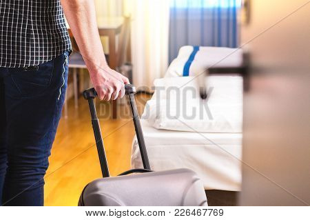 poster of Man Pulling Suitcase And Entering Hotel Room. Traveler Going In To Room Or Walking Inside Motel With