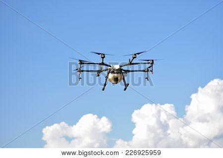Flying Agriculture Drone, Photo Image Of Agriculture Drone Carry A Tank Of  Liquid Fertilizer Flying poster