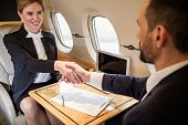 Contented Young Businesswoman Shaking Hands With Her Companion In Airplane, Contract Is Lying On Tra poster