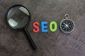 Magnifier Glass, Colorful Alphabet Seo And Compass On Dark Chalkboard Background Using As Seo Search poster